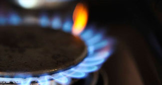 blue gas stove flame with one orange flame