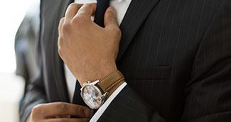 Corporate man fastening neck tie